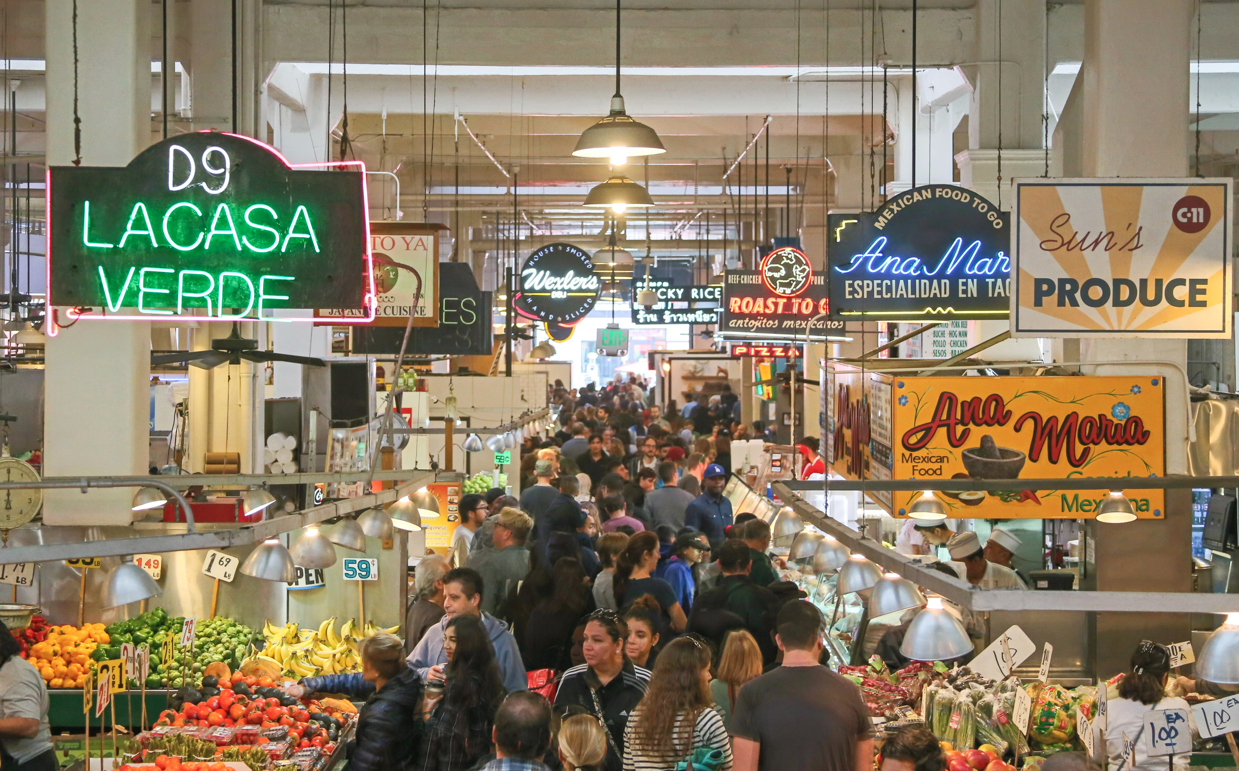 Los Angeles, United States - November 28, 2015: A view looking down into the Grand Central Market in historic downtown Los Angeles. Here you can find a large variety of food stands and stalls selling groceries and other food related items. Located in the historic Homer Laughlin building, it features a large open space for shopping and browsing and various neon signs advertising foods traditionally found in California. People can be seen shopping and sitting at counters eating meals.